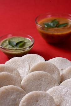 Idli mit sambar und kokosnusschutney auf rotem hintergrund, indisches gericht