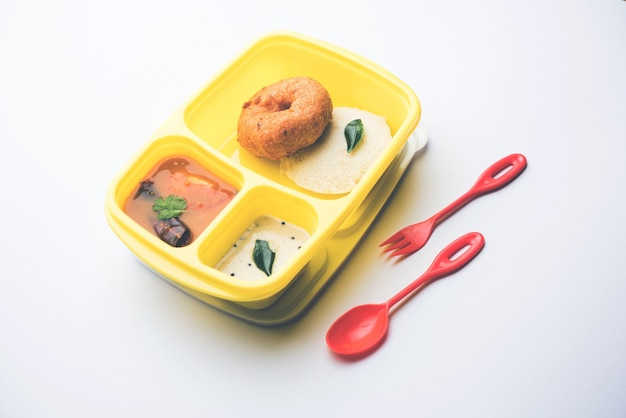 Idly oder idli mit medu wada sambar in der lunchbox tiffin
