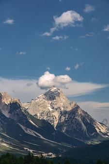 Idyllische alpen mit felsigem berg unter blauem himmel