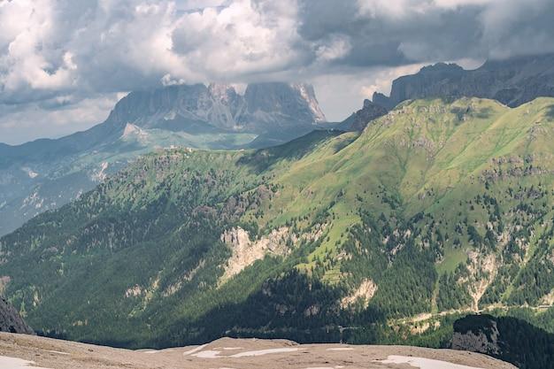 Idyllische alpen mit grünem hügel unter wolkenhimmel