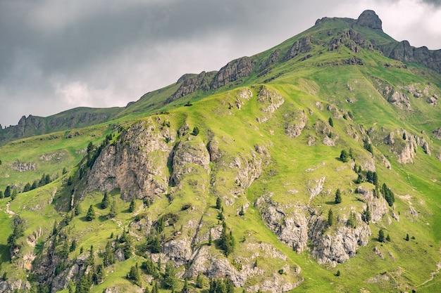Idyllische landschaft mit hohem grünem hügel unter himmel