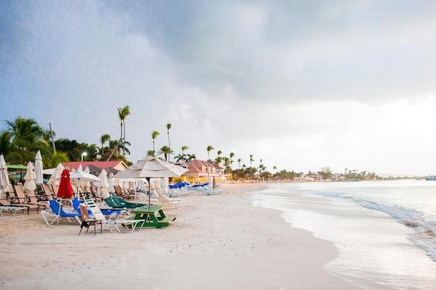 Idyllischer karibischer tropischer strand mit weißem sand, türkisozeanwasser vor dem regen
