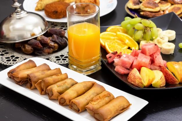 Iftar buffet. frühlingsrolle, früchte, frischer orangensaft, samosa-snack, frühlingsrolle und pfannkuchen