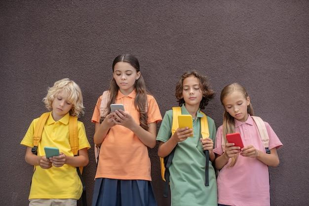 Igen. vier kinder spielen online-spiele auf ihren smartphones