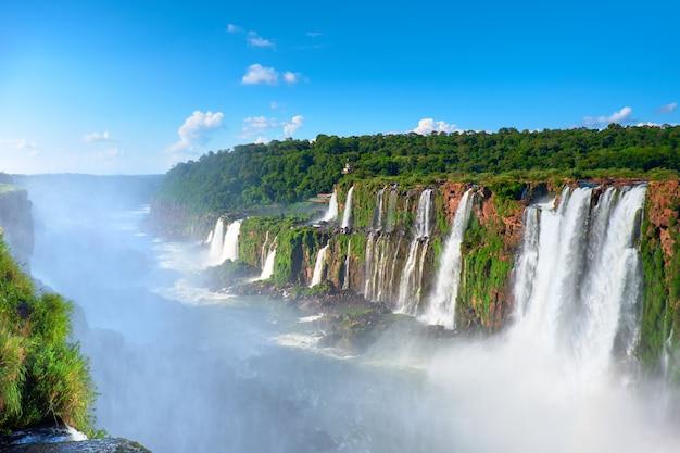 Iguazu-wasserfälle in argentinien, blick vom teufelsmund auf einen sonnigen tagesnebel vom fallenden wasser. kraftvolles wasser dampft über dem fluss iguazu.