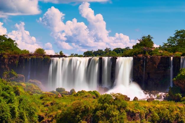Iguazu-wasserfälle in argentinien, blick von devil's mouth, nahaufnahme einer mächtigen wasserkaskade, die nebel über dem iguazu-fluss erzeugt. getöntes bild mit streulicht. subtropischer regenwald.