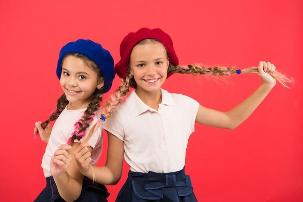 Ihr eigener stil. mädchen im französischen stil. nette mädchen mit der gleichen frisur. kleine kinder mit langen haarzöpfen. mode mädchen mit gebundenen haaren in zöpfe. kleine kinder, die stilvolle französische baskenmützen tragen.