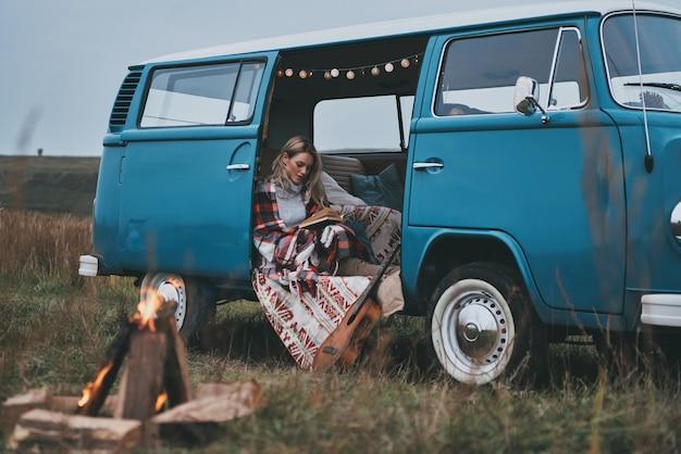 Ihr lieblingsbuch genießen. attraktive junge frau bedeckt mit decke, die ein buch liest, während sie innerhalb des blauen retro-stil-minivans sitzt