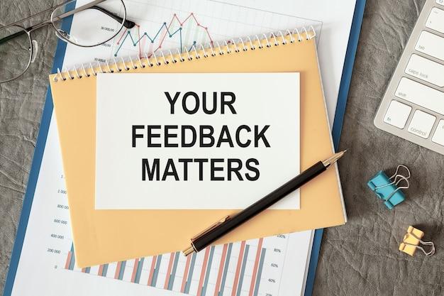 Ihre feedback-angelegenheiten werden in einem dokument mit bürozubehör auf dem schreibtisch geschrieben.