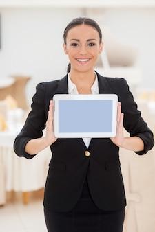 Ihre nachricht auf ihrem tablet. attraktive junge frau in formeller kleidung, die ihr digitales tablet zeigt und lächelt, während sie im restaurant steht