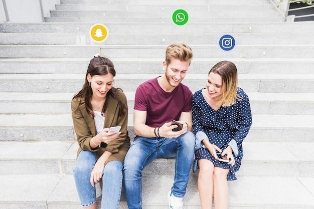 Ikone des sozialen netzes über den glücklichen freunden, die handy verwenden