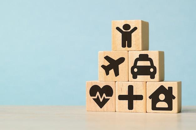 Ikonen auf hölzernen spielzeugblöcken gestapelt in pyramidenform. konzeption einer körperlichen untersuchung für das gesundheitswesen und die krankenversicherung. das konzept der versicherung