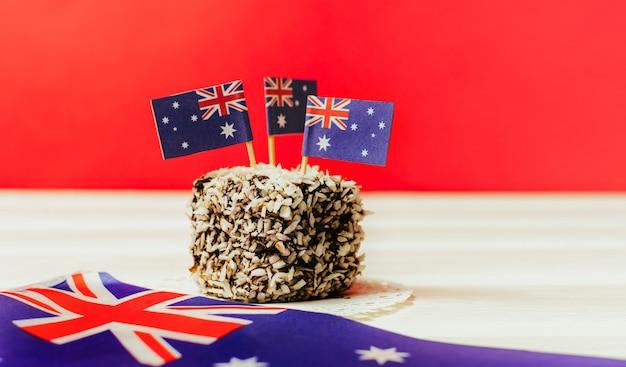 Ikonenhaftes traditionelles australisches partyessen, lamington-kuchen auf einem roten, weißen und blauen hintergrund. australien flagge.