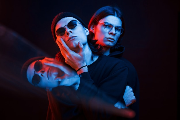 Illusion von drei gesichtern. porträt von zwillingsbrüdern. studioaufnahme im dunklen studio mit neonlicht