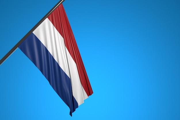 Illustration der nationalflagge der niederlande auf einem metallfahnenmast, der gegen den blauen himmel flattert