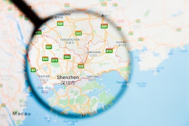 Illustratives konzept der stadtvisualisierung von shenzhen, china auf anzeigebildschirm durch lupe