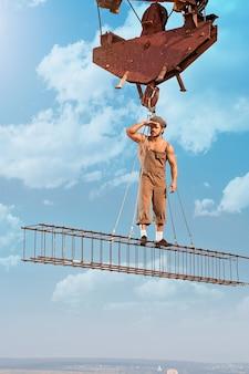 Im auge behalten. junger hemdloser bauarbeiter im alten stil, der wegschaut, stehend auf einer querstange, die an einem kran an einem wolkenkratzer hängt?