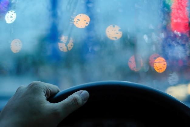 Im auto hand greifen lenkrad und regen tröpfchen auf der windschutzscheibe mit unscharfen boke fest