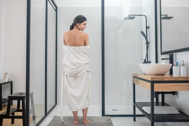 Im badezimmer. ein dunkelhaariges junges mädchen in einem weißen bademantel im badezimmer
