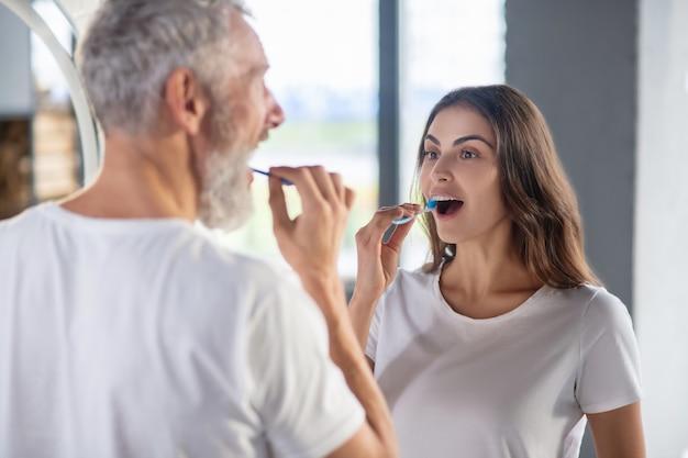 Im badezimmer. eine frau und ein mann putzen sich morgens die zähne