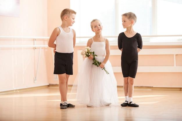 Im ballett-tanzkurs: jungen und ein mädchen mit blumen, die anmutig posieren