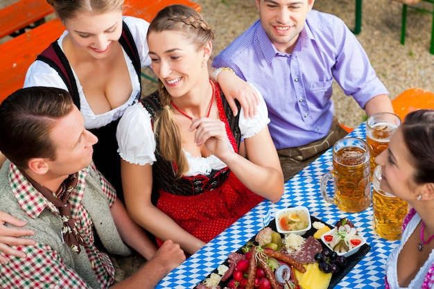 Im biergarten - freunde auf einem tisch mit bier