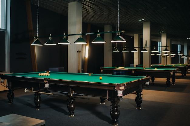 Im billardclub gibt es viele billardtische mit grünen oberflächen und bällen.