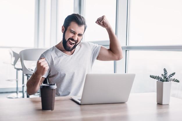 Im büro sitzt der geschäftsmann am schreibtisch, beendet das projekt mit laptop und gewinnt groß. macht erfolgreiche gesten, hebt die arme zum feiern. seine tasse kaffee steht vor ihm