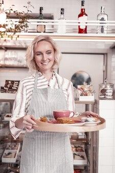 Im café. erfreute fröhliche kellnerin, die lächelt, während sie ein tablett mit frühstück hält
