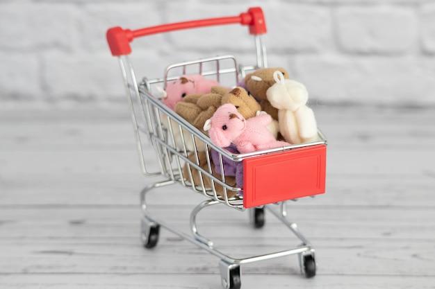 Im einkaufswagen liegen viele bunte spielzeug-teddybären. einkaufen auf dem markt. geschenke für geburtstage und feiertage kaufen.