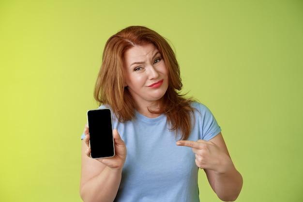 Im ernst, es ist schrecklich unzufrieden, enttäuscht, rothaarig, reif, weiblich, kippend, verzieht das gesicht und zeigt nur ungern auf den zeigefinger des leeren smartphones, der ein schlechtes foto zeigt