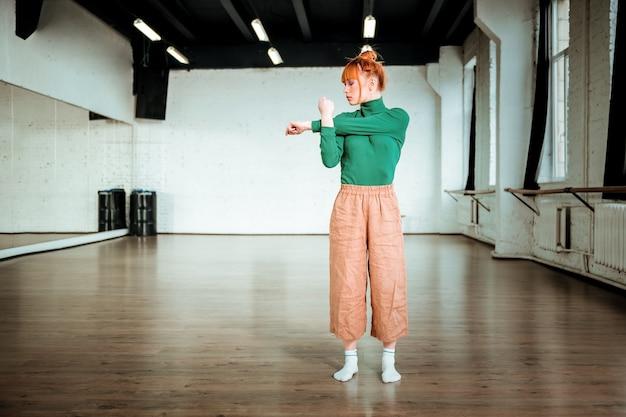Im fitnessstudio. rothaariges junges mädchen, das einen grünen rollkragenpullover trägt, der in einem fitnessstudio trainiert