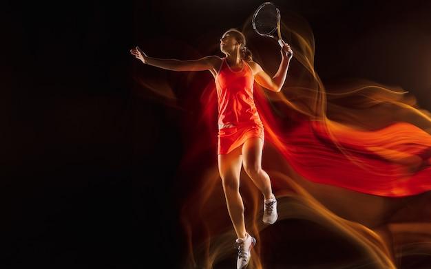 Im flug. professionelles weibliches tennisspielertraining isoliert auf schwarzem studiohintergrund in gemischtem licht. frau im sportanzug üben. gesunder lebensstil, sport, training, bewegung und aktionskonzept.
