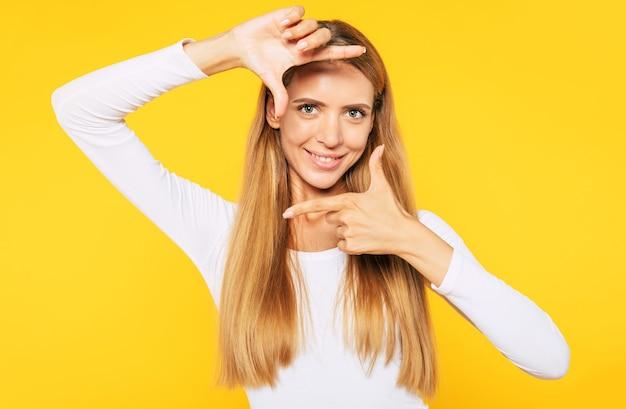 Im fokus. aufgeregte, glückliche, schöne blonde frau posiert über gelber wand und macht mit ihren händen eine schießgeste