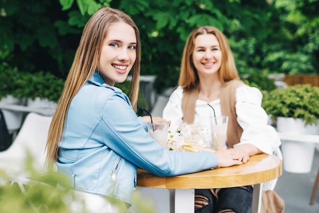 Im fokus lächelt ein junges blondes mädchen in die kamera und hält die hand ihrer mutter