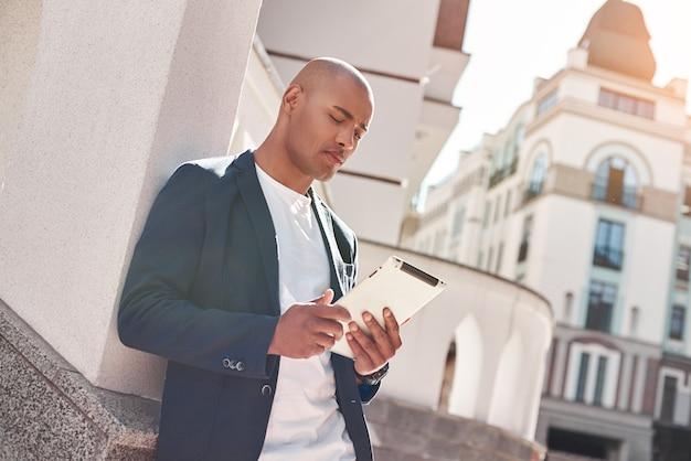 Im freien freizeit junger mann, der auf der stadtstraße steht und sich an die wand lehnt und im internet surft