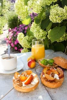 Im freien frühstück mit gegrillten brötchen mit ziegenfett, obst, nüssen, orangensaft und kaffee