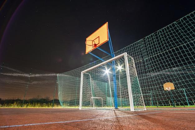 Im freien mini-fußball- und basketballplatz mit balltor und korb, umgeben von einem hohen schutzzaun, der nachts hell mit scheinwerferlampen beleuchtet wird.