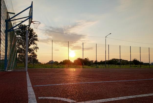 Im freien mini-fußball- und basketballplatz mit balltor und korb, umgeben von hohem schutzzaun.