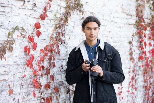 Im freien porträt des männlichen fotografen, der nahe weißer hintergrundwand hält, die dslr-kamera hält, die kamera betrachtet