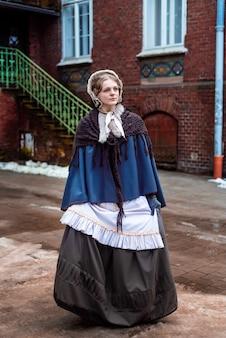 Im freien porträt einer jungen viktorianischen frau, die alte stadt geht