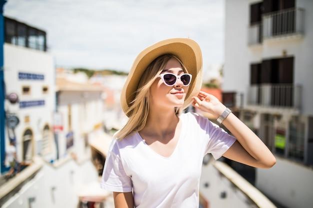 Im freienmodeporträtmädchen, das hut trägt, trendige sonnenbrille, die auf handlauf sitzt