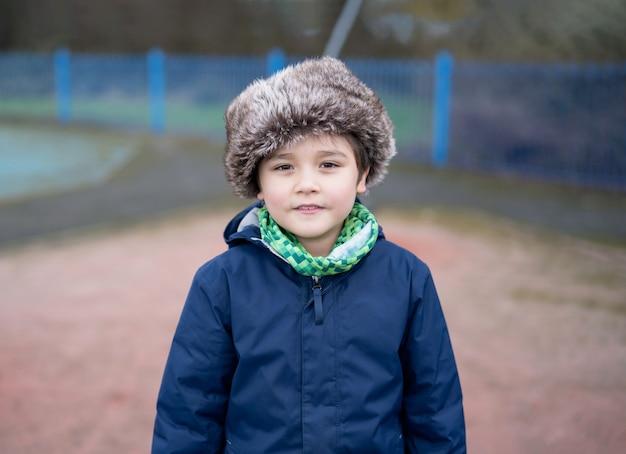 Im freienporträt niedlicher junge lächelnd, glückliches kind, das draußen im spielplatz spielt