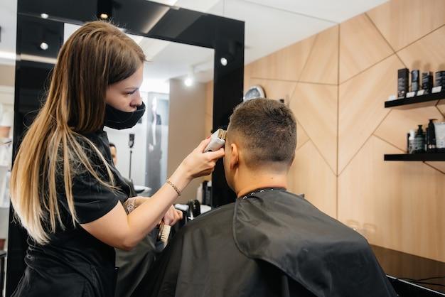 Im friseursalon schneidet und rasiert der meister den mann