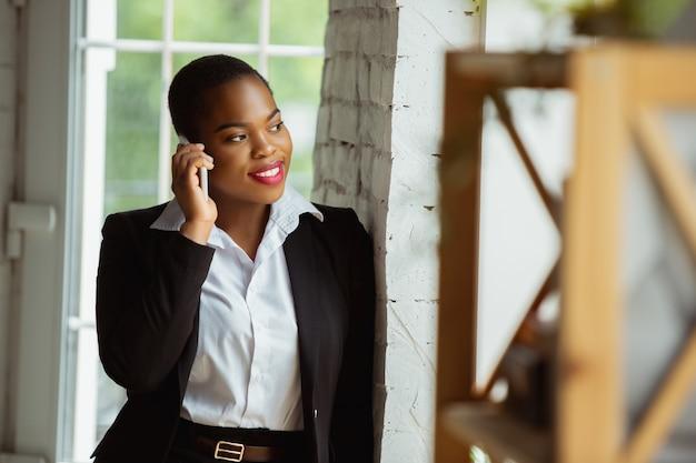 Im gespräch mit partnern. afroamerikanische geschäftsfrau in bürokleidung lächelnd, sieht selbstbewusst und glücklich aus. konzept für finanzen, wirtschaft, gleichstellung und menschenrechte. schönes junges weibliches modell, erfolgreich.