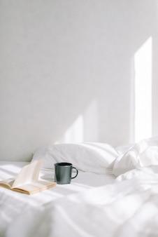 Im hellen schlafzimmer auf dem bett steht ein offenes altes buch neben einer tasse kaffee oder tee. vor dem hintergrund der sonnenstrahlen. vertikales foto
