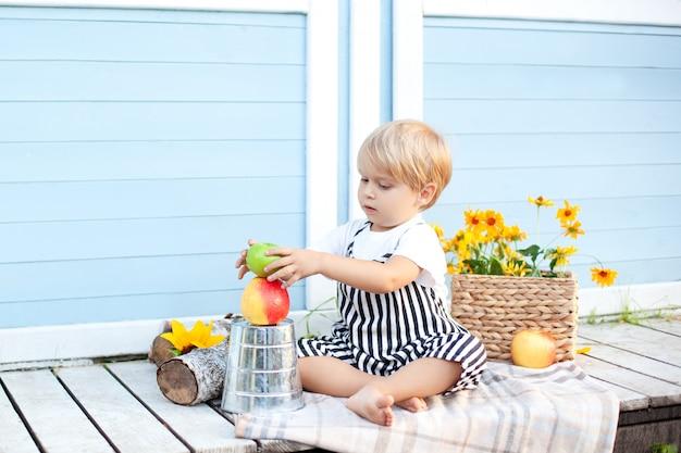 Im herbst spielt ein kind auf dem hof. ein blonder kleiner junge sitzt auf der veranda eines landhauses und spielt mit früchten. kindheitskonzept. glückliches kind. ernte. kleiner bauer. picknick-mittagessen)