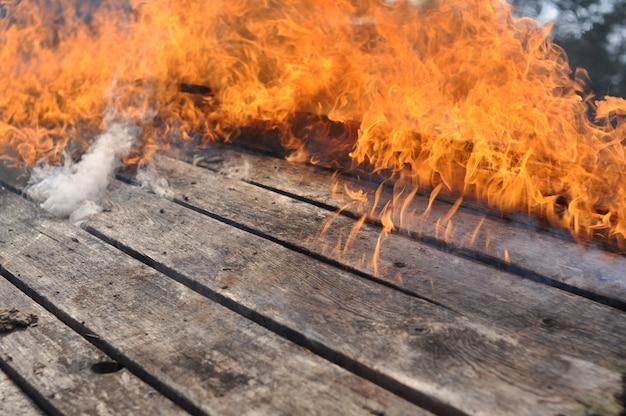 Im hintergrund der holzbretter des hauses brennt eine große feuerflamme