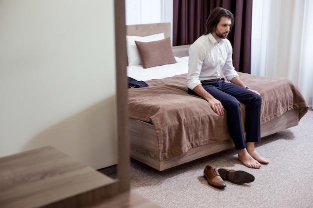Im hotelzimmer. trauriger müder mann, der auf dem bett im hotel sitzt, während er sehr müde ist