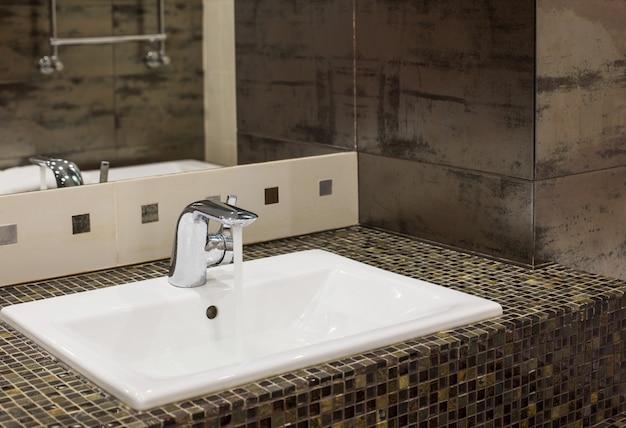 Im inneren des badezimmers fließt wasser aus dem wasserhahn